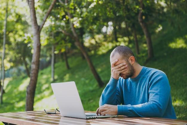 カジュアルな青いシャツを着た若い疲れた悲しい男のビジネスマンや学生、ラップトップを使用して都市公園で携帯電話でテーブルに座って、屋外で作業し、問題を心配しています。モバイルオフィスのコンセプト。