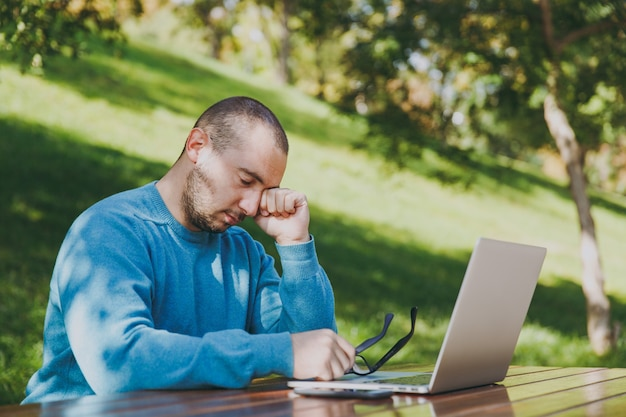 Young tired sad man businessman or student in casual blue shirt, glasses sitting at table with mobile phone in city park using laptop, working outdoors, worries about problems. mobile office concept.