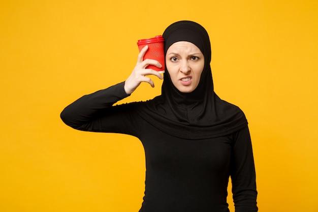 ヒジャーブの黒い服を着た若い疲れた悲しい動揺アラビアのイスラム教徒の女性は、黄色の壁の肖像画に分離されたコーヒーの紙コップを保持します。人々の宗教的なライフスタイルの概念。