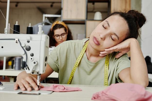 Молодая усталая швея с рулеткой на шее сидит у электрической швейной машины с закрытыми глазами и имеет короткий перерыв