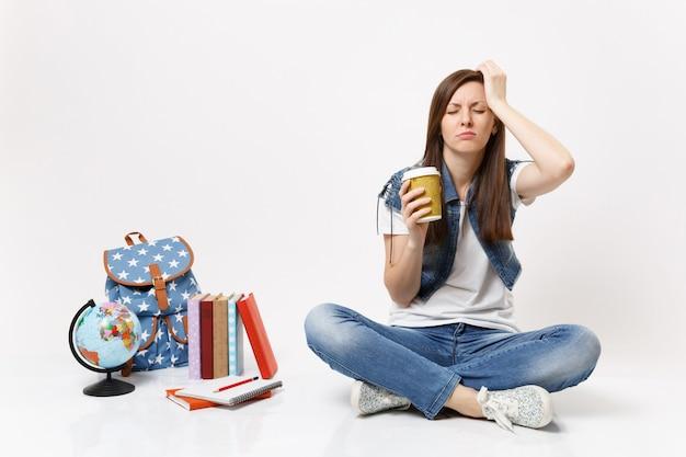 Giovane studentessa stanca e assonnata tiene un bicchiere di carta con caffè o tè tenendo la mano sulla testa seduta vicino allo zaino del globo, libri di scuola isolati