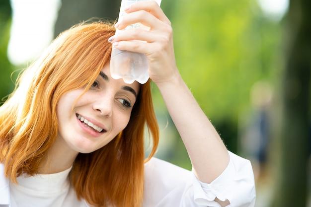 若い疲れて笑顔赤毛の女性は夏の公園でボトルから水を飲む