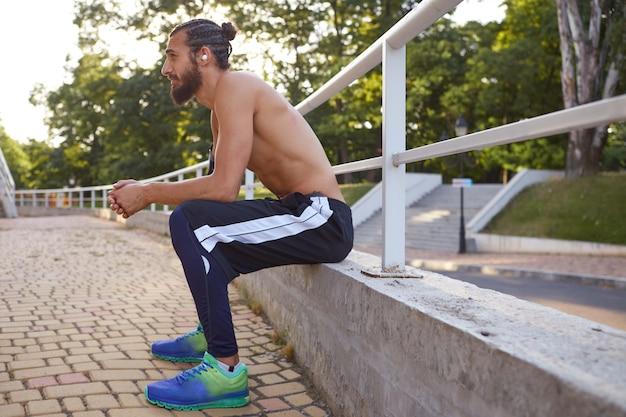 Молодой усталый спортивный бородатый мужчина занимается экстремальным спортом в парке, отдыхает после пробежки, смотрит в сторону.