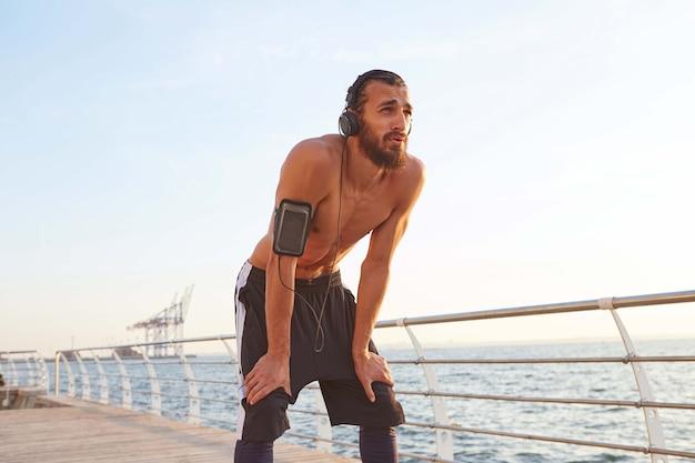 Молодой усталый спортивный бородатый молодой парень отдыхает после пробежки на берегу моря, слушая любимую музыку в наушниках.