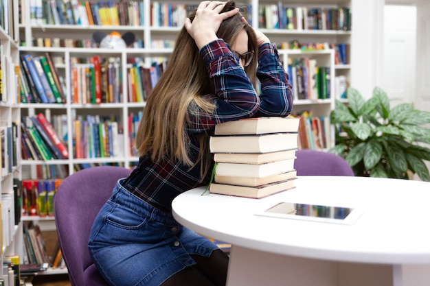Young tired student girl sitting in a library at a table leaning on a large pile of books.