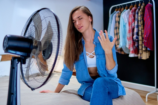 Young tired sweaty woman sitting on bed in the bedroom in sunny hot summer day in the front of working fan