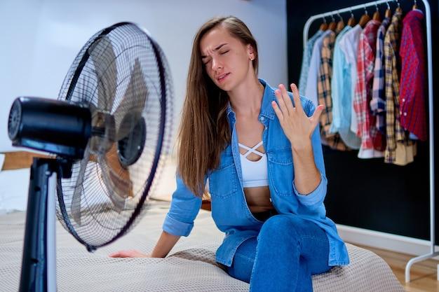 働くファンの前で晴れた暑い夏の日に寝室のベッドに座っている若い疲れた汗まみれの女性