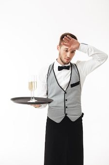 Young tired waiter in uniform holding tray with glasses of champagne while thoughtfully