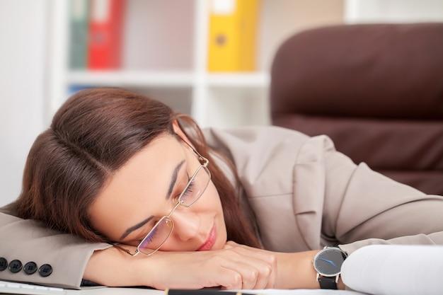 Молодая женщина устала на рабочий стол, спать с закрытыми глазами