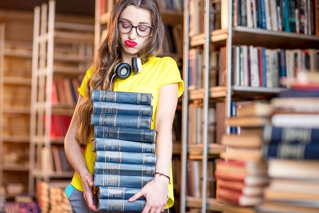 Young tired woman carrying a heap of books at the old library