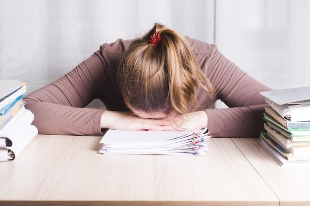 Молодая усталая женщина-фрилансер на домашнем офисном столе спит