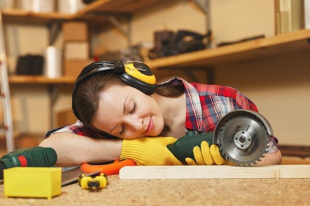 格子縞のシャツ、灰色のtシャツ、遮音ヘッドフォン、さまざまなツールを使用して木製のテーブルの場所で大工仕事のワークショップで働いている黄色い手袋、パワーソーで木で寝ている若い疲れた女性。