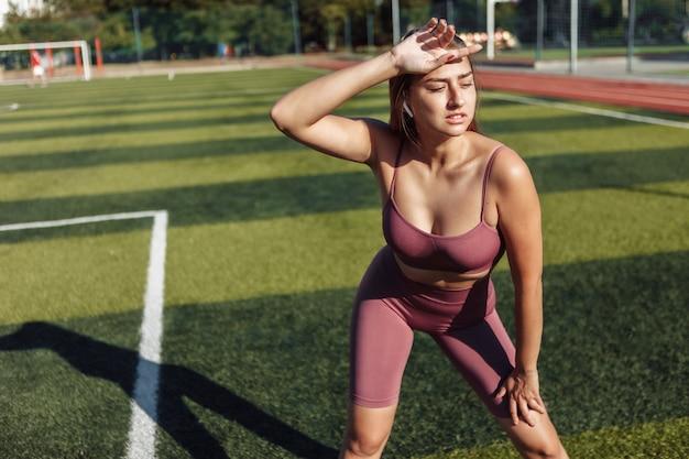 スタジアムでスポーツウェアの若い疲れた女性。明るい晴れた日。屋外トレーニング
