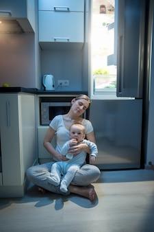 Молодая усталая женщина сидит на полу на кухне ночью и кормит ребенка из бутылочки