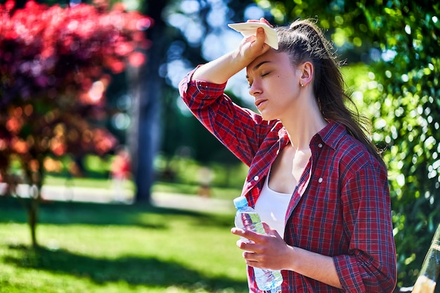 夏の日の屋外の暑さで苦しんでいる若い疲れた女性