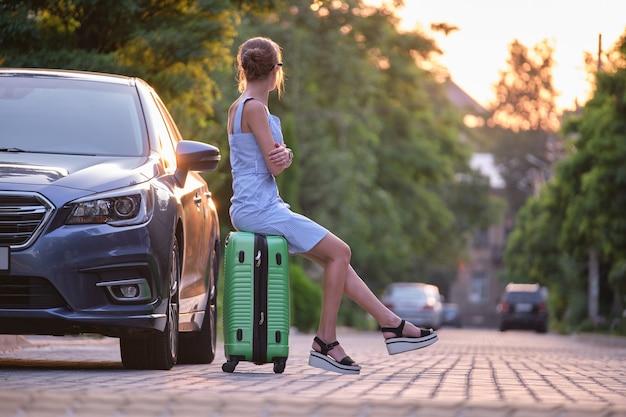 누군가를 기다리는 차 옆에 앉아 가방을 들고 젊은 피곤한 여자. 여행 및 휴가 개념입니다.