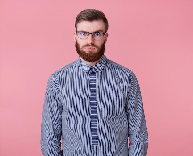 Giovane stanco del lavoro un ragazzo barbuto con gli occhiali e una camicia a righe guarda lontano, pensa a quanti altri progetti chiudere e se avrà tempo, isolato su sfondo rosa.