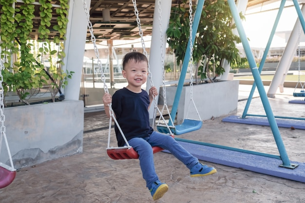 Young toddler boy child having fun swinging at children playground