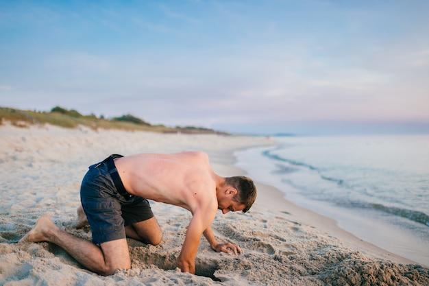 夏の夜に膝の上に立って海の向こうのビーチで手でピットを掘るショートパンツの若いトップレス裸足男。