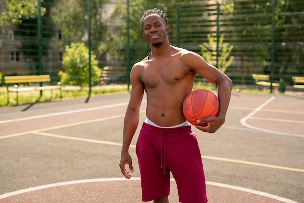 コートや都市環境のスポーツグラウンドにボール立って若いトップレスバスケットボール選手