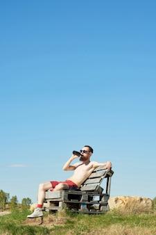 Молодой бородатый топлес мужчина пьет пиво, сидя на деревянной скамейке на открытом воздухе на фоне ясного голубого неба