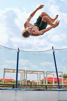 Young topless sportsman in green shorts jumping over trampoline surrounded by net against cloudy sky in natural environment