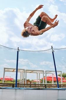 Молодой спортсмен топлес в зеленых шортах прыгает через батут в окружении сетки на фоне облачного неба в естественной среде