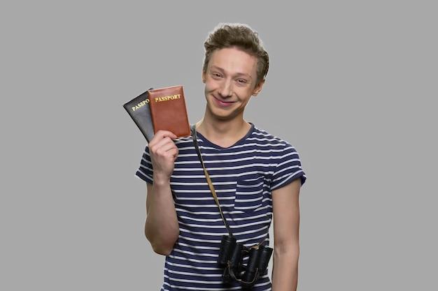 パスポートを示す若い観光客の少年。灰色の背景にパスポートを保持している幸せな笑顔の10代の少年。旅行の準備ができました。