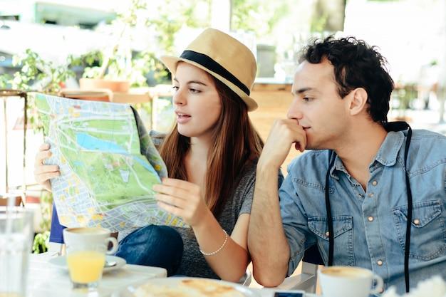 若い観光客のカップルが地図を見ています