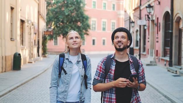 Молодая туристическая пара гуляет по улице и делает фотографии на смартфоне. они любуются красотой окрестностей.