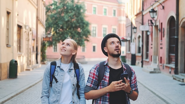 Young tourist couple walking on the street and making photos on smartphone. they admiring the beauty of surroundings.