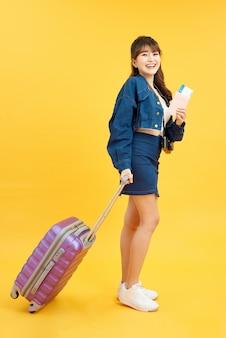 紫色のスーツケース、パスポート、黄色の背景で隔離のチケットと夏のカジュアルな服を着た若い観光客の女の子