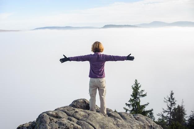 바위 위에 서있는 젊은 관광 소녀