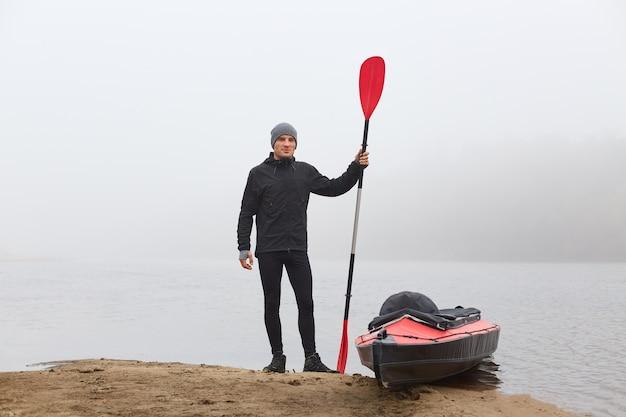 Молодой турист в теплой спортивной одежде стоит на берегу реки и собирает каяк для путешествия по туманной реке