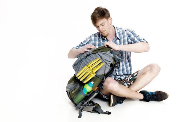 Молодой турист сидит и смотрит в рюкзак что-то на белом фоне. путешественник готовится к походу