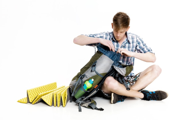 Young tourist is sitting and looking in a backpack something on a white background. the traveler is preparing for a hike