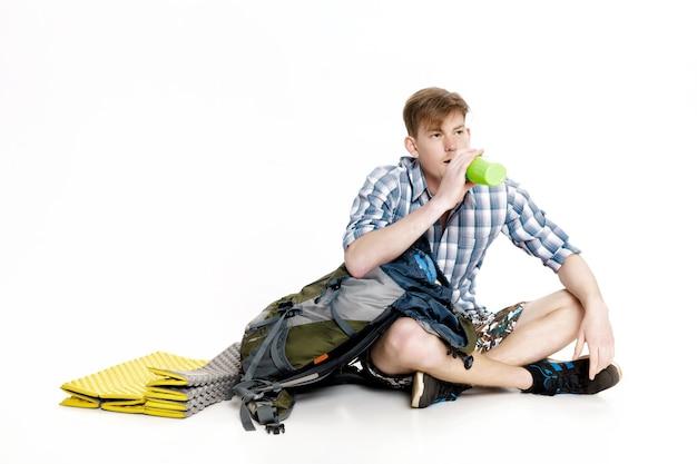 Молодой турист сидит с рюкзаком и питьевой водой на белом фоне. путешественник готовится к походу