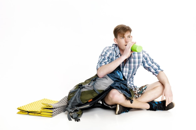 Young tourist is sitting with backpack and drinking water on the white background. traveler is preparing for hike