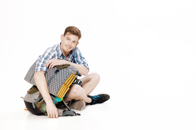 Young tourist is sitting with backpack on white background traveler is preparing for hike