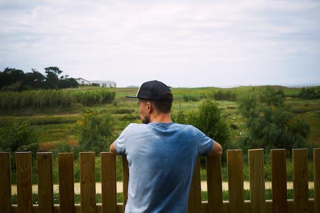 Молодой турист, глядя на зеленый пейзаж, стоящий за забором