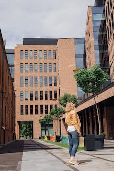 若い観光客は、都市建築の背景に非常に有機的に見えます都市景観touri ...