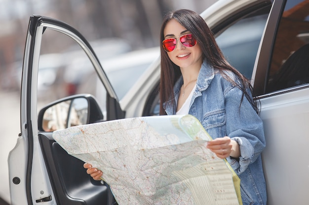 Young tourist lost in town. woman holding map. driver got lost. navigation in the alien city.