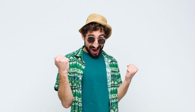 Молодой турист, чувствуя себя счастливым, удивленным и гордым, крича и празднуя успех с большой улыбкой на белой стене
