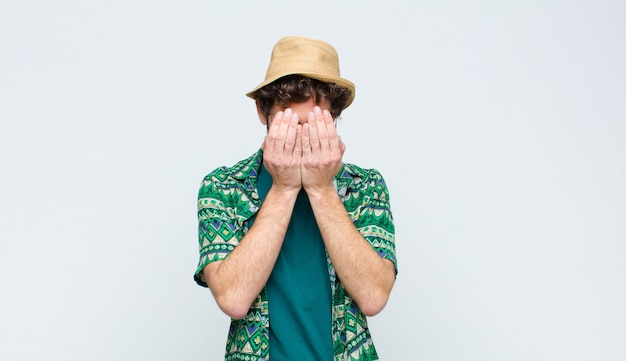 Young tourist man feeling sad, frustrated, nervous and depressed, covering face with both hands