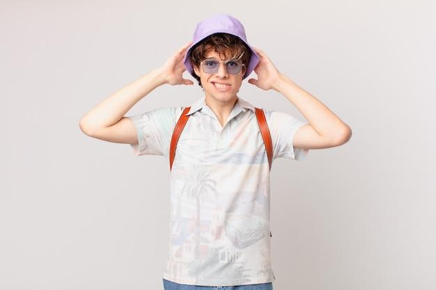 頭に手を置いて、ストレス、不安、または恐怖を感じている若い観光客の男性