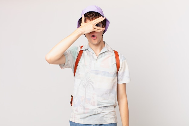 ショックを受けたり、怖がったり、恐怖を感じたり、手で顔を覆っている若い観光客の男性
