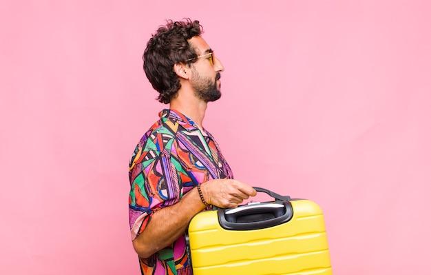 Молодой турист человек на виде профиля с чемоданом, концепция путешествия