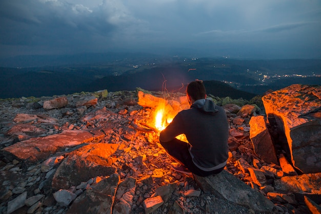 Young tourist man sitting on summer night at bright fire on rocky mountain top under cloudy sky.