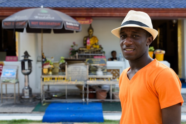 Young tourist man smiling against view of the shrine of buddha displayed with offerings and incense in wat arun temple