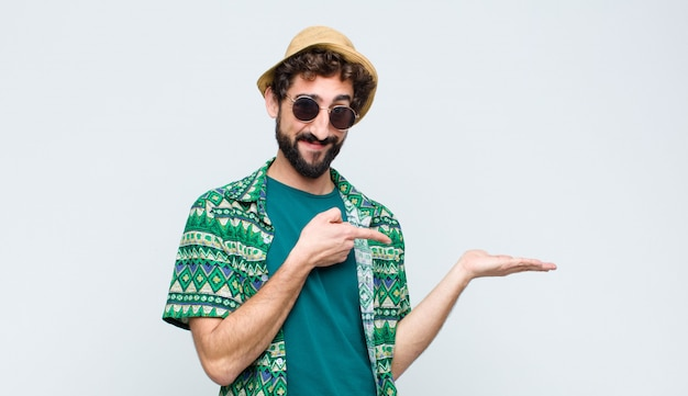 Молодой турист человек улыбается, чувствуя себя счастливым, беззаботным и довольным, указывая на сторону над белой стеной